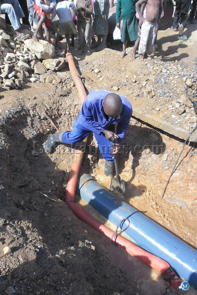 Lusaka Water and Sewerage worker fixing a leaking pipe