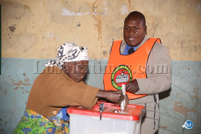 ssistant presiding officer Christopher moyo assisting a 78 year old woman of Katete district during the mkaika by elections in Katete yesterday