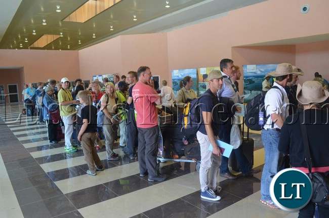 Tourists and UNWTO delegates line up to have their travel documents checked inside the arrival hall of the new international terminal building in Livingstone