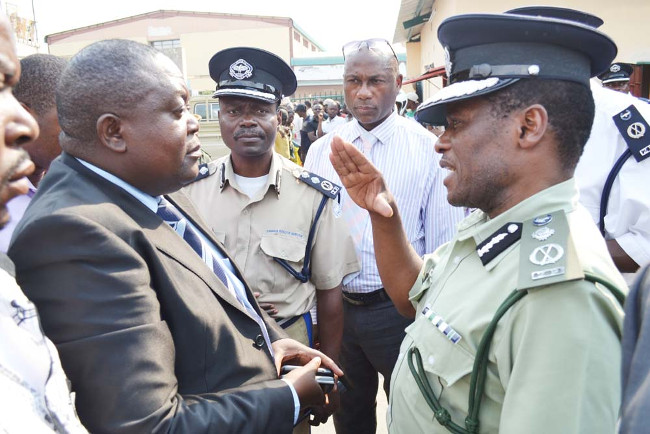 DEPUTY Inspector-General of Police Solomon Jere (right) talks to newly-appointed Patriotic Front (PF) interim District chairperson Robert Chikwelete at the ruling party's District office premises