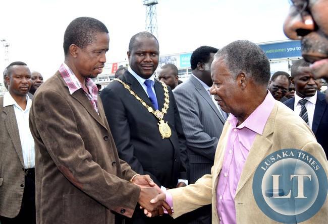 President Sata greets Defence minister Edgar Lungu  on arrival at Kenneth Kaunda International Airport i
