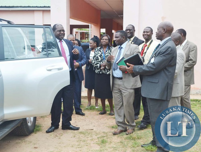 Health Deputy Minister Chitalu Chilufya (right) talks to University Teaching Hospital managing director Lakson Kasonka (in dark grey suit,right), as others look on after officiating at the handover of three buses and one utility vehicle worth K1.8 million in Lusaka