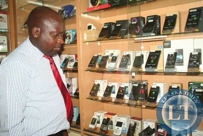 CYCORP Managing Director, Kingsley Nkonde, who also leads the fight against counterfeit products in Zambia, checks some Samsung mobile phones at Mobile City Shop in Chipata. This was when the Eastern Province Intellectual Property Unit (IPU) in conjunction with Samsung Brand owners checked for counterfeit products