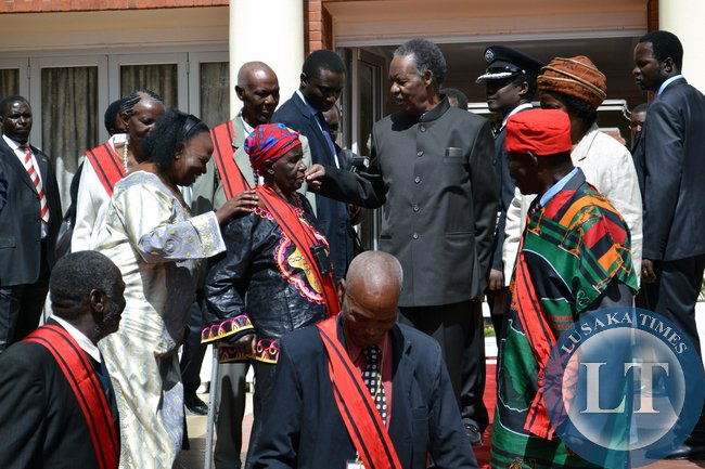 President Michael Sata talks to Veronica Tembo, who was honoured with the Grand Commander of the Companion Order of Freedom as he interacted with those honoured during an investiture ceremony at State House.