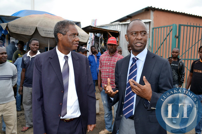Local Government Minister Emmanuel Chenda (left) listens to Lusaka Mayor Mulenga Sata during a tour of Lusaka town centre market