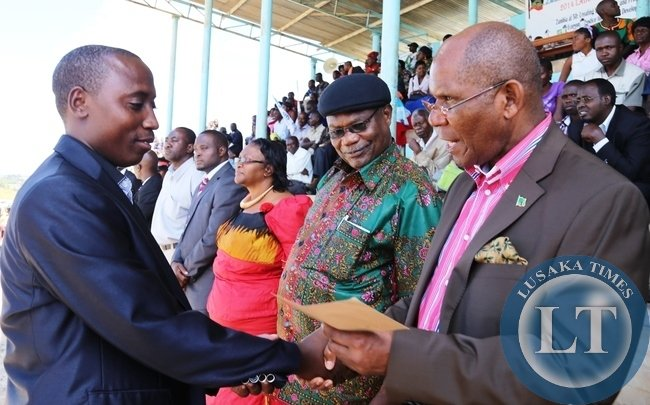 Commerce Trade, and Industry Minister Bob Sichinga gives out cash to AMICO employee Brian Ndalama as Luapula Province Minister Benson Kapaya looks on