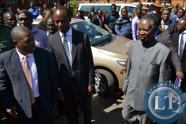 President Michael Sata is accompanied by Justice Minister Wynter Kabimba (left) and Lusaka Mayor Mulenga Sata as he left the Lusaka High Court