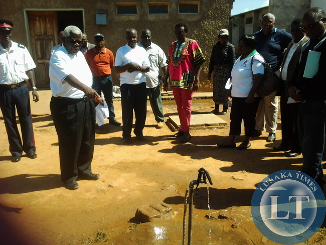 Deputy secretary to cabinet Ambassador Peter Kasanda pointing at a broken down tap whose water was running at youth skills resource Centre in Mumbwa