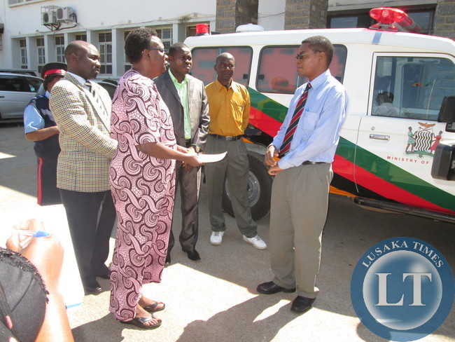 Central province Permanent Secretary Edwidge Mutale receiving keys from Acting Provincial Medical Officer George Chibulu for the ambulance donated to Luano district.