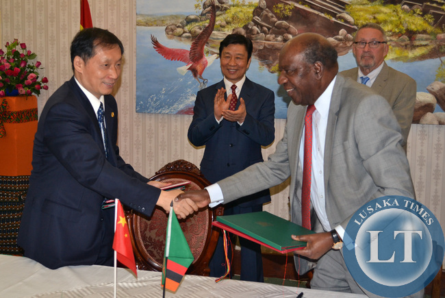 Finance Minister Alexander Chikwanda shakes hands with Chinese Vice Minister of Commerce Li Jinzao (left) after signing various agreements in the presence of Vice President Guy Scott and Chinese Vice President Li Yuanchao (second from left) look on at Government House in Lusaka