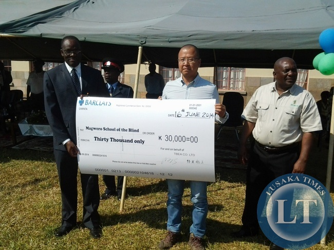 Eastern Province Permanent Secretary Dr Chileshe Mulenga, TBEA Deputy Project Manager Meng Lei and ZESCO regional manager Yobe Mukonka holding a dummy cheque of Magwero School of the Blind in Chipata yesterday.The K30,000 was donated to the school as part of commemoration on African Day