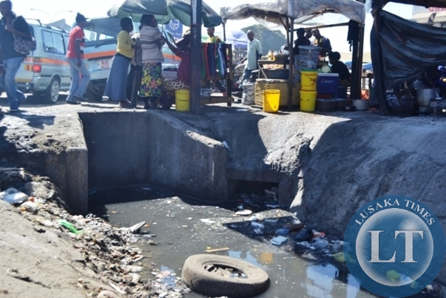Second hand clothes traders seemingly used to the chocking smoky environment were waste is indiscriminately disposed and burnt at Lusaka's City Market