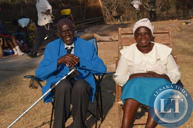 Timothy Hatyoka (left) and his wife Elizabeth (right) outside their house in Hamukanchali Village in Monze District during his 100th birthday celebrations
