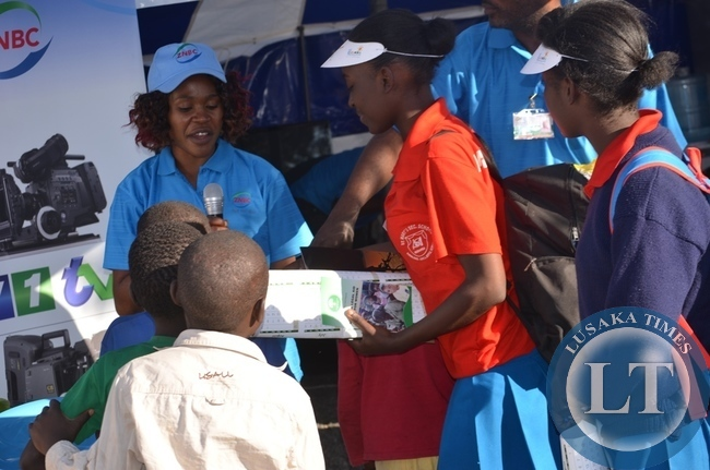ZNBC's Mercy Ngoma (far left) interviewing pupils (right) at the company pavilion in Livingstone at the just ended 8th Southern Tourism, Agricultural and Commercial Show Society (STACSS)