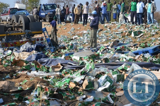 Some onlookers helplessly watch the remains of spilt imported beer products in Livingstone