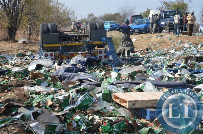 Some onlookers helplessly watch the remains of spilt imported beer products in Livingstone .This was after a foreign truck with registration number N74152W overturned near Zambia Wildlife Authority (ZAWA) entrance to Mosi-oa-tunya National Park along Livingstone-Kazungula road