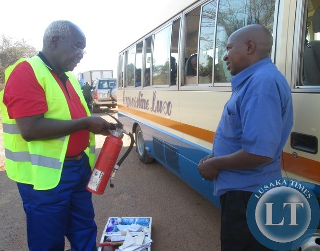 captions Communications and Transport Deputy Minister Panji Kaunda yesterday mounted a Road Block at Prospect police Camp near Kabwe where he Impouded a number of Vehicles which had faults .In the picture, Mr Kaunda inspects the fire Extinguisher from a Rosa Bus while the Driver of a Bus looks on