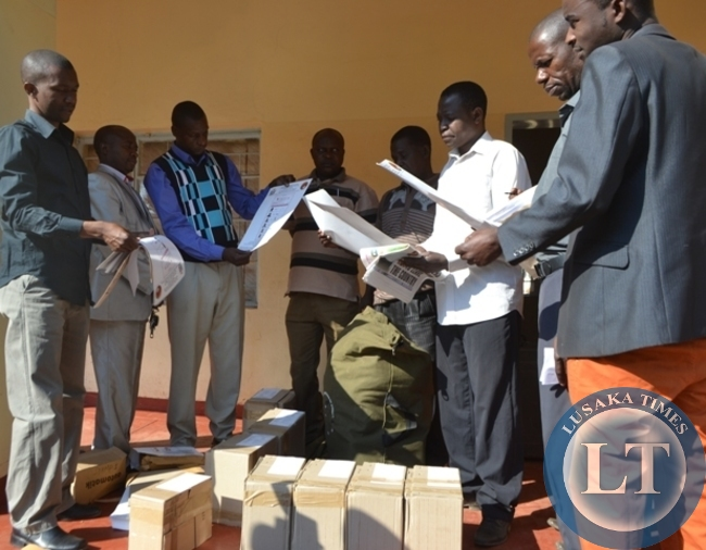 Mangango constituency returning officer, Kingsley Mutayachalo (left) unveils voting material at Kaoma civic centre