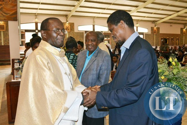 Defence Minister Edgar Lungu (right) shakes hands with Archbishop of Lusaka Telesphore Mpundu (left) as Finance Minister Alexander Chikwanda looks on at the memorial service of the aate Benjamin Mwila at the Cathedral of the Chile Jesus