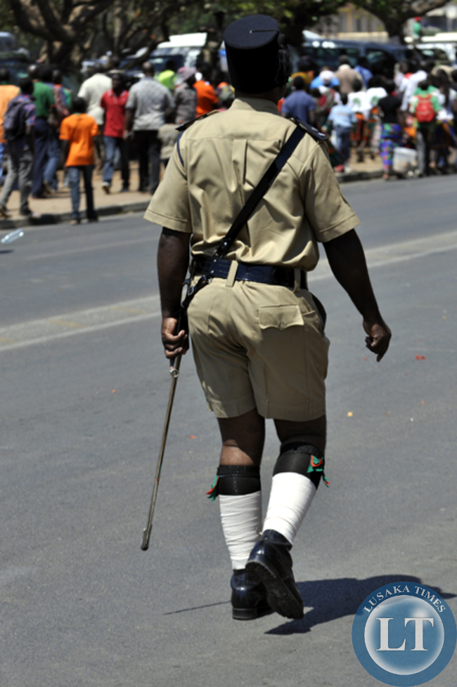 An unidentified man dressed in colonial style police uniform makes his way at during the independence day march past in Lusaka