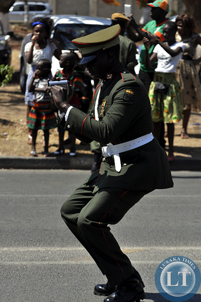 An unidentified military man shooting video of Zambian troops at the freedom statue