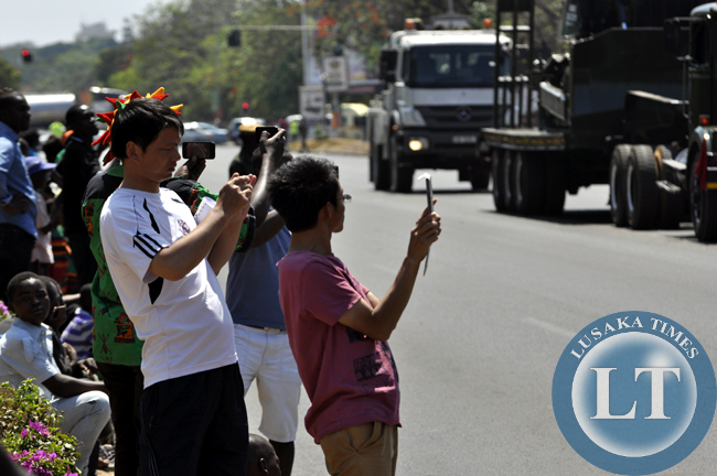 Chinese nationals take photographs of proceedings during the independence day march past in Lusaka