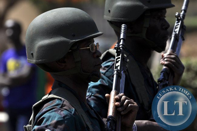 Zambia National Service troops carrying guns during the independence day march past at the freedom statue in Lusaka