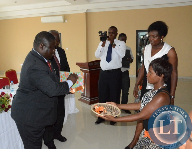 Transport and Communication Minister Yafya Mukanga receives scissors From African Direction Performer whilst RDA Senior Public Relation Manager loyce Saili looks on during the launch of Road Maintenance Strategy 2015-2024 book