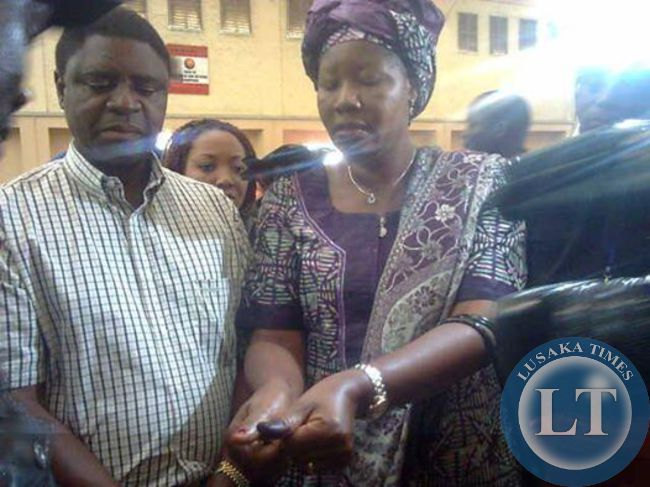 Edith Nawakwi flanked by her husband Hambulo shows her  nails after she managed to cast her vote