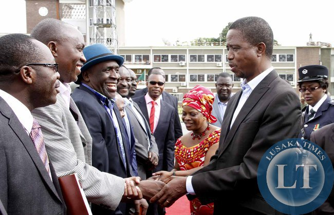 President Edgar Lungu greets Goodward Mulubwa as  his  Special Assistant for  Political Affairs Kaiza Zulu looks on  on arrival at Kenneth Kaunda International Airport shortly before departure to Addis Ababa, Ethiopia for the African Union Summit on January 29,2015 -Picture by THOMAS NSAMA