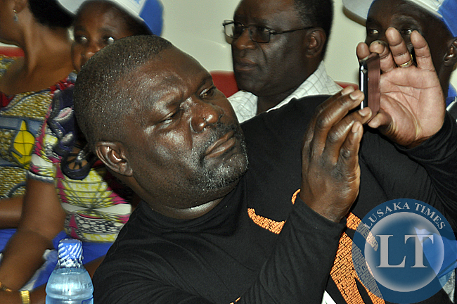 Lucky Mulusa using his smart phone to capture pictures during the press conference where Rupiah Banda announced his support for Edgar Lungu in the January 20, 2015 elections
