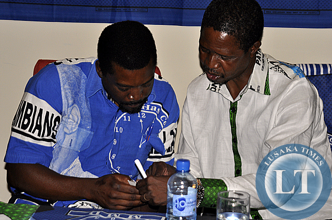 PF presidential candidate Edgar Lungu (r) confers with MMD national secretary Muhabi Lungu during the press conference where Rupiah Banda announced his support for the PF candidate