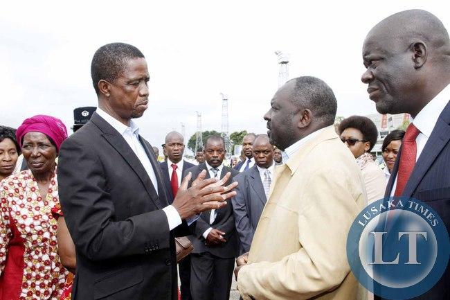 President Edgar Lungu talks to PF Secretary General Davies Chama as Home Affairs minister Davies Mwila (r) looks on  at Kenneth Kaunda International Airport shortly before departure to Addis Ababa, Ethiopia for the African Union Summit on January 29,2015 -Picture by THOMAS NSAMA