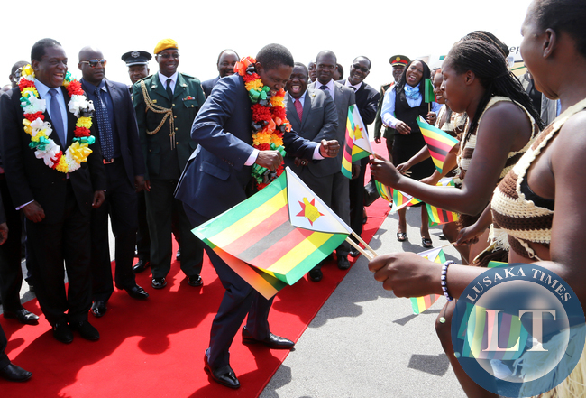 President Edgar Lungu joins in the dance looking on is Zimbabwean vice President Minister Emmerson Mnangagwa at Harare, Zimbabwe. Picture By EDDIE MWANALEZA /STATEHOUSE