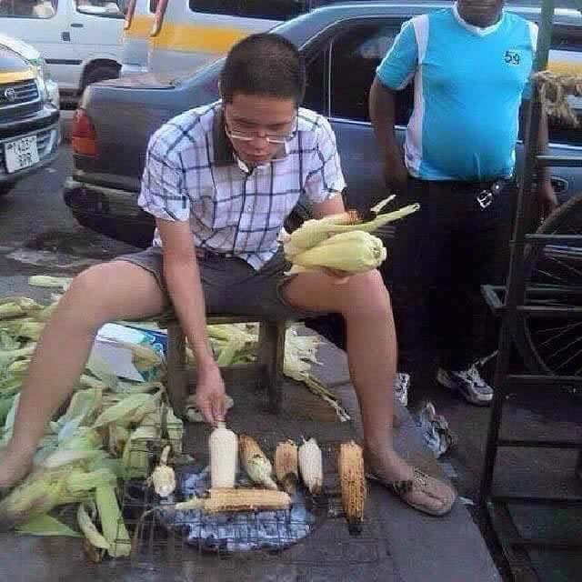 Chinese man selling roasted maize
