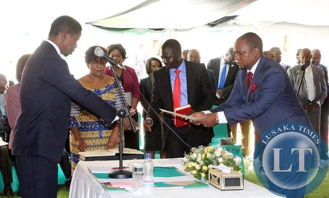 President Edgar Chagwa Lungu (left) receives an affidavit of Oath from Newly appointed Commerce Deputy minister Miles Sampa during the Swearing-In-Ceremony at State House on February