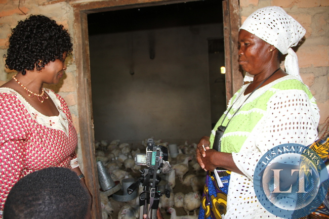 First Lady Esther Lungu  checks on the Chickens as Kaole women club coordinator Charity Katebe (r)   looks on   when she visited Kaole Chisapa women Club in Luapula Province.  This was during the  First Lady's Outreach Programme for People with Special Needs in Mansa on February 27,2014 -Picture by THOMAS NSAMA