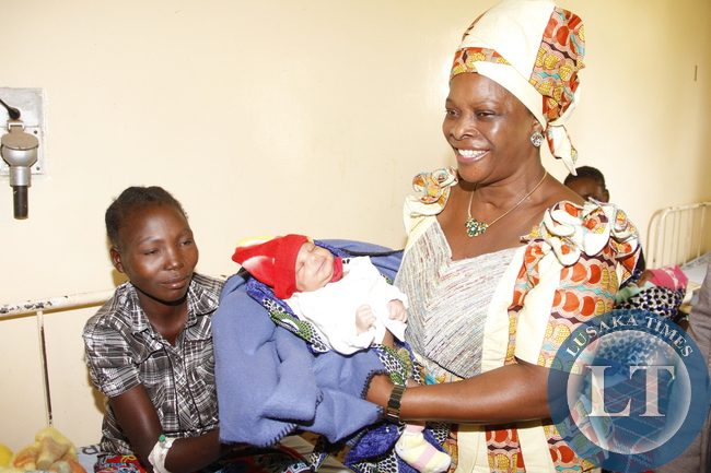 First Lady Esther Lungu admires a baby  at Mbala General Hospital  where she visited patients on March 2,2015 -Picture by THOMAS NSAMA