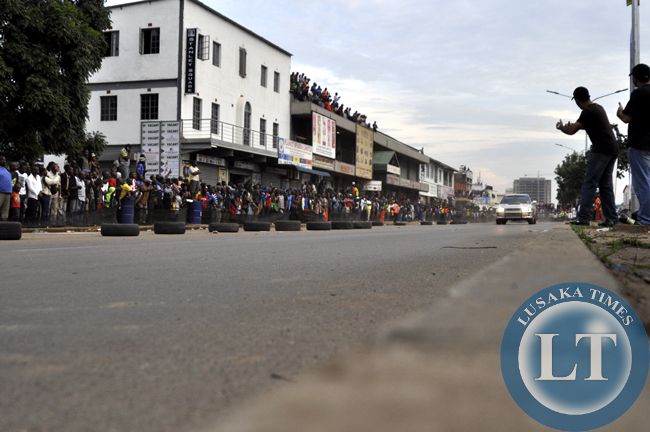 Revellers cheer a speeding rally driver