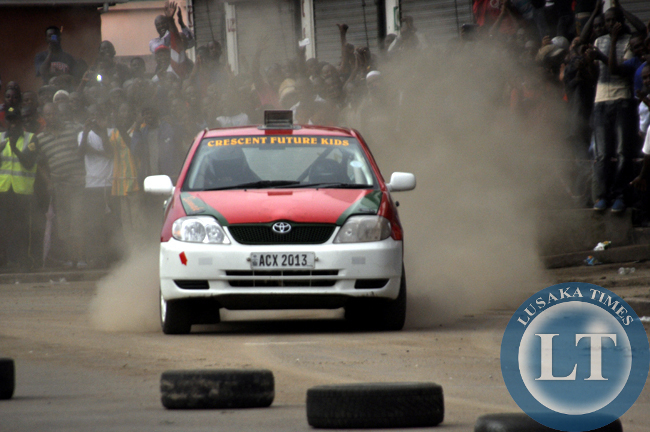Spectators cheering a rally driver cruising along freedom Way