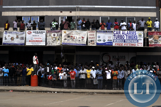Spectators watching rally cars from roof tops and along shop corridors