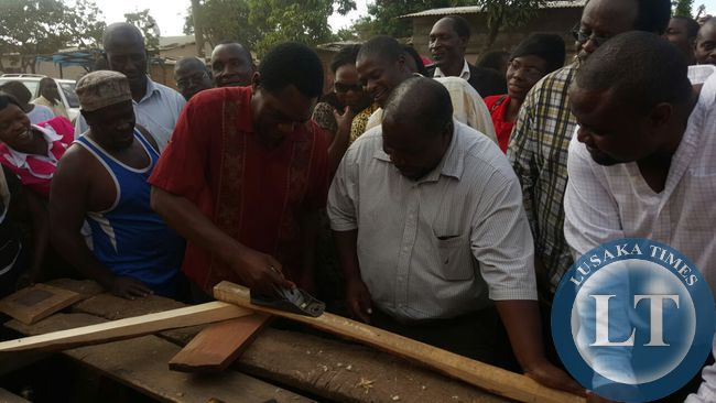 UPND president Hakainde Hichilema interacts with carpenters in  Bauleni compound