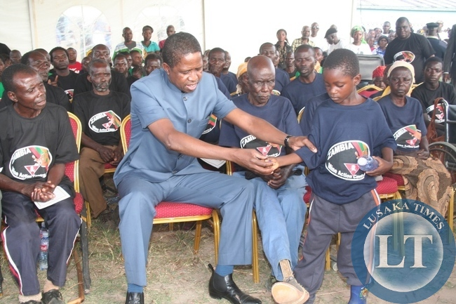 President Lungu  eight year old land mine survivor Gift Mutebula during the photo session with the land mine survivors at Kalene school grounds