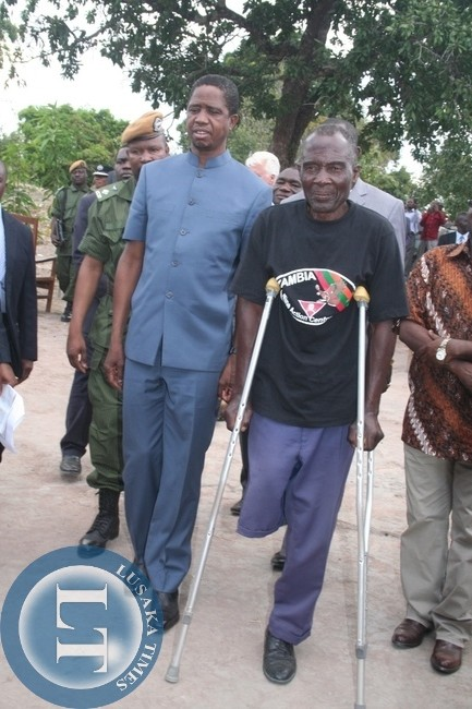 President Edgar Lungu walking side by side with a land mine survivor Enock Makabi AT Nyeka Village in Ikeleng'e district
