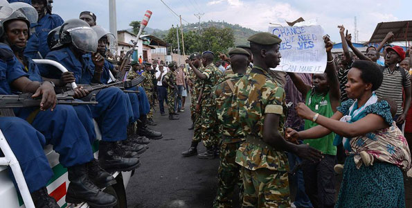 Burundian soldiers control protesters facing riot police seated in a pickup truck in Musaga, on the outskirts of Bujumbura, on April 29, 2015, during demonstrations against the President's bid for a third term. Since the protests started, the army has regularly come between the police and demonstrators to avoid further clashes and the protesters believe the soldiers are neutral. AFP PHOTO   SIMON MAINA