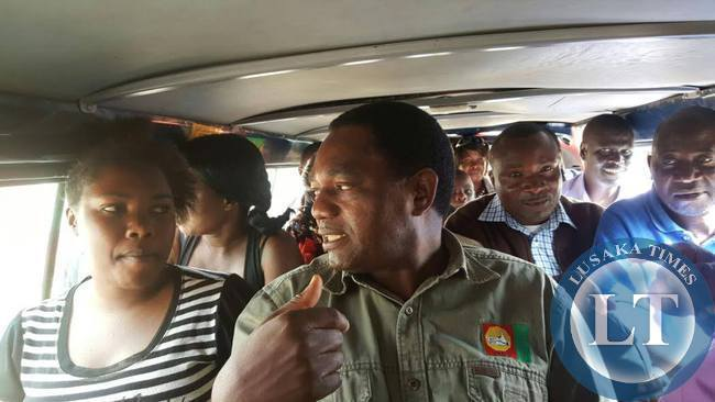UPND president Hakainde Hichilema interacts with passengers a minibus going to Mandevu