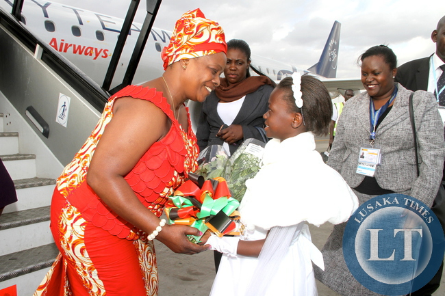 First Lady Esther Lungu receives a bouquet of flowers from Mama Ngina Childrens Home on arrival at Jomo Kenyatta International Airport  for the 9th Stop Cervical, Breast and Prostate Cancer in Africa Conference in Nairobi on July 18,2015 -Picture by THOMAS NSAMA