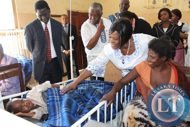 First Lady Esther Lungu (c) seeing a child patient as Western Province Medical Officer Dr. Andrew Silumesii (l) looks on at Lewanika General Hospital during the commissioning of a relatives' shelter constructed with the support of the Ministers' Wives Club in Mongu