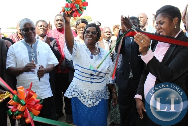First Lady Esther Lungu (c) cuts the ribbon to officially open a new Lewanika General Hospital Relatives' Shelter constructed with the support of the Ministers' Wives Club in Mongu