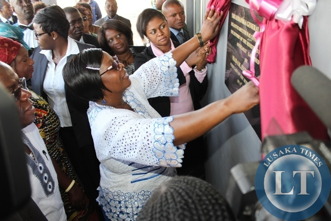 First Lady Esther Lungu (c) unveils the plaque to officially open a new Lewanika General Hospital Relatives' Shelter constructed with the support of the Ministers' Wives Club in Mongu